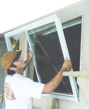 You are about to see a picture Brent installing a replacment window in a typical stucco house. This window is a simple no grids (dividers, mulliuns, cris cross squares , what ever you want to call'em).  This is a simple installation, Brent will take about a hour per window. Windows with brick, wood, shutters or any thing like that will take just about 10 minutes longer. On those windows he needs to trim the edge of the window flange to fit. The result is a great looking window that ties into your wood or bricks ect.